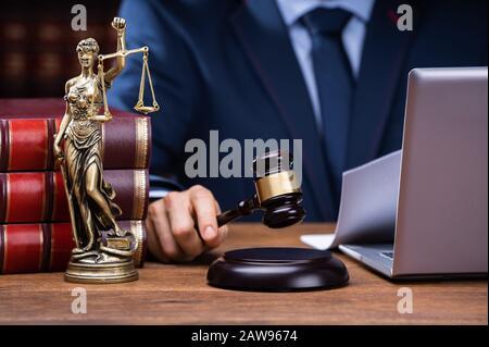 Section Intermédiaire Du Juge Frappant Gavel Près De Mallet Et Ordinateur Portable Au Bureau À Courtaom