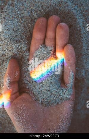 Main féminine avec poignée de sable et réflexion de l'arc-en-ciel, gros plan. Banque D'Images