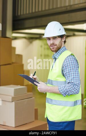 Portrait du jeune travailleur regardant l'appareil photo tout en se tenant près des boîtes et en prenant des notes dans le document