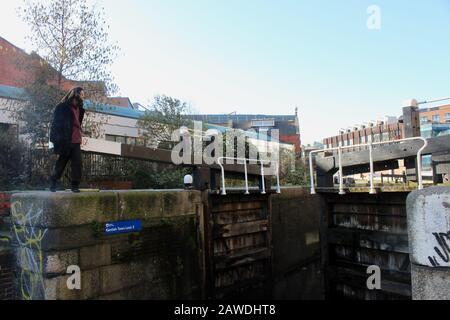 Un homme fermant les portes de la écluse après avoir traversé sa barge à camden londres angleterre Royaume-Uni Banque D'Images