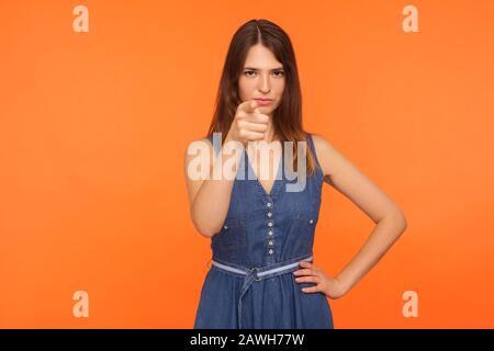 Hé toi ! Femme brunette très mécontente dans une robe en denim pointant le doigt vers l'appareil photo et regardant avec une expression en colère suspecte, faisant accusant gestu Banque D'Images