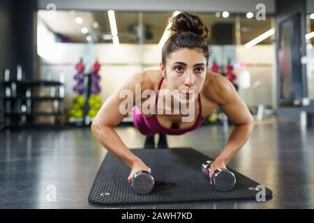 Woman doing push-ups exercice avec haltère dans un entraînement de fitness