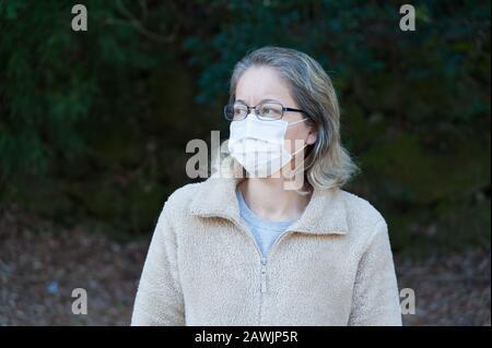 Belle femme mixte (brésilienne / japonaise) cheveux brun clair portant des lunettes et un masque chirurgical pour la protection antivirus. Vue latérale. Banque D'Images