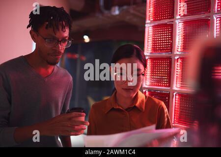 Groupe multiethnique de personnes d'affaires discutant de documents en se tenant à l'extérieur dans un éclairage rouge sombre, espace de copie