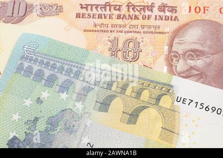 Une orange, dix Indiens rupee bill, Close up avec un bleu et vert 5 euros note de la France Banque D'Images