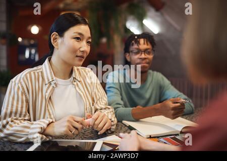 Groupe multiethnique de trois personnes d'affaires travaillant sur le projet tout en étant assis à la table dans un café, espace de copie