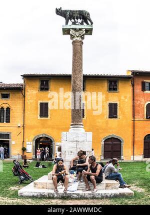Italie.Pise.Toscane.(Toscana).Les Touristes profitent d'une pause déjeuner sous la statue du loup Capitolin de Rome.. Banque D'Images