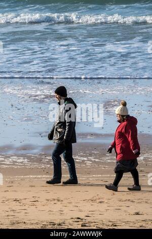 Les gens qui apprécient de marcher le long de la rive à Fistral Beach en fin d'après-midi, à Newquay, en Cornwall. Banque D'Images
