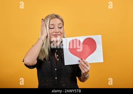 heureuse femme dans l'amour tenant un morceau de papier avec coeur rouge tenant main sur la tête Banque D'Images