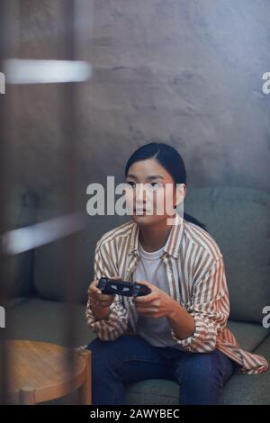 Portrait vertical de la jeune femme asiatique jouant des jeux vidéo via une console de jeu Banque D'Images