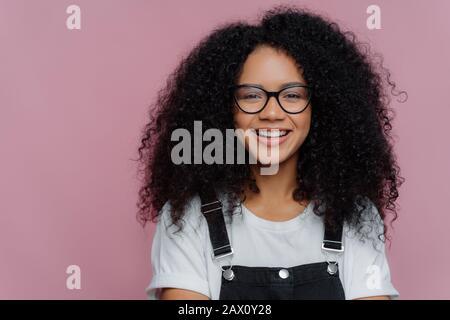 Gros portrait d'une femme à peau foncée avec des cheveux nets, sourires heureux, porte des lunettes optiques, vêtements décontractés, pose sur fond violet exprime Banque D'Images