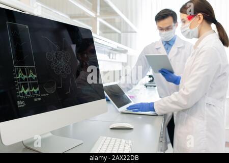 Tir horizontal de deux scientifiques portant des manteaux, masques et gants blancs travaillant en laboratoire à l'aide d'ordinateurs et de gadgets Banque D'Images