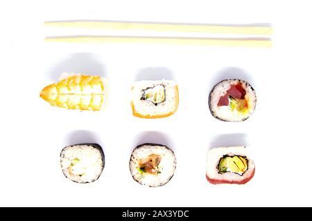 Un ensemble de rouleaux de différents types avec des bâtons de sushi isolés sur un fond noir
