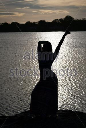 Belle jeune femme blonde pose devant une petite cascade dans le parc souriant avec la main sur la hanche Banque D'Images
