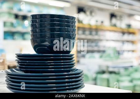 les articles ménagers sont disposés sur les étagères pour la vente. Assiettes, tasses, bols, dans les tons de bleu classique.assiettes et plats bleus, design moderne.céramique Banque D'Images