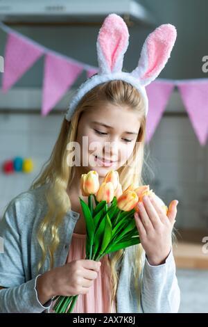 Gros plan portrait de petite fille mignon portant des oreilles de lapin et tenant un bouquet de tulipes Banque D'Images
