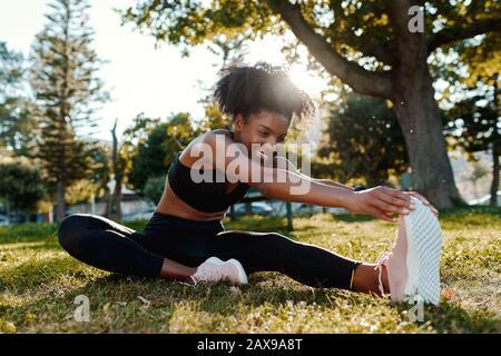 Portrait souriant d'une jeune femme afro-américaine de taille sportive assise sur une pelouse qui s'étire sur ses jambes dans le parc - heureuse jeune femme noire se réchauffe