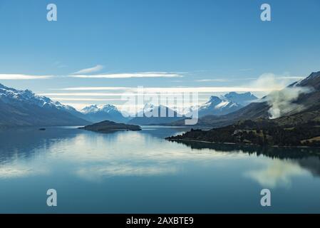 Vue sur le lac Wakatipu vers Glenorchy, Nouvelle-Zélande avec de la fumée qui s'élève d'un petit feu de brousse Banque D'Images