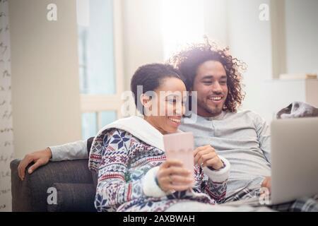 Couple affectueux dans un pyjama relaxant, utilisant un ordinateur portable sur un canapé Banque D'Images