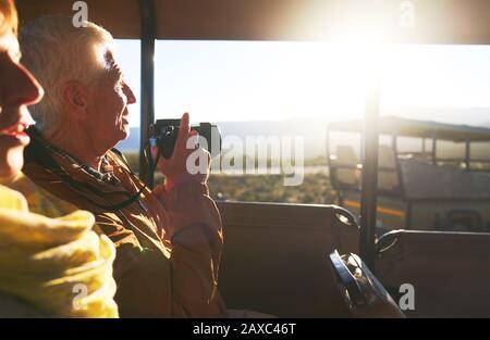 Couple senior avec appareil photo numérique en véhicule tout-terrain safari Banque D'Images