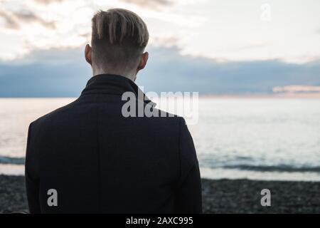 Un jeune taille masculine dans un manteau se trouve au bord de la mer ou de l'océan et bénéficie d'un coucher de soleil. Automne au bord de la mer sur une plage rocheuse Banque D'Images