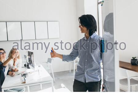 Développeur asiatique debout près du tableau de conférence et regardant une fille blonde dans des lunettes. Portrait intérieur d'un homme d'affaires brunette écrivant un graphique à bord blanc et écoutant des collègues. Banque D'Images