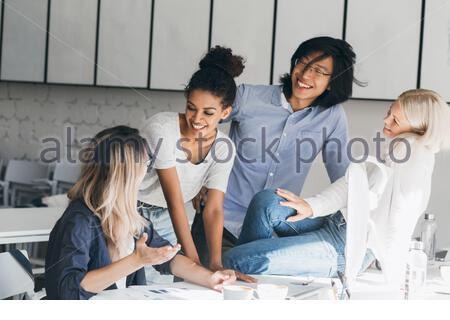 Une fille blonde souriante en Jean assise sur le bureau et regardant le jeune homme chinois alors que la femme programmeur indépendant plaisante. Portrait intérieur de heureux étudiants buvant du café dans la salle de conférence. Banque D'Images