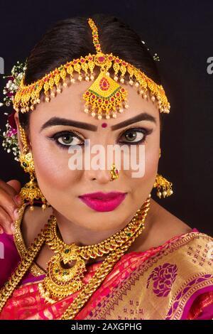Portrait d'une jeune et belle femme indienne bengali brunette en sari traditionnel rouge et blanc Banque D'Images