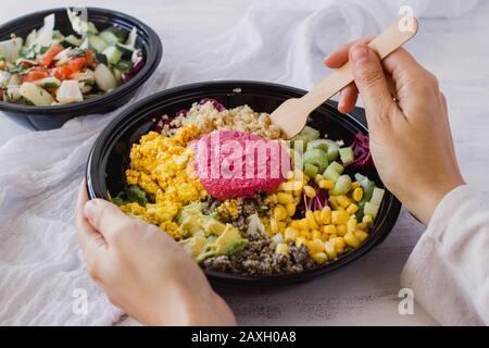 Concept de nourriture saine de bol de Bouddha. Salade de détox végétalien avec le quinoa et l'houmous de betterave sur fond blanc. Style Instagram avec manger les mains