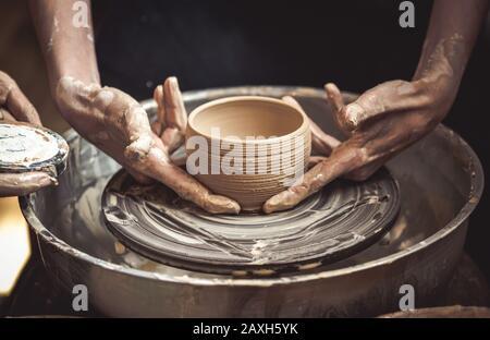 Un pot d'argile brute dans les mains d'un potter. Maître crock.