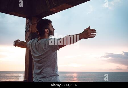 Homme qui ouvre ses bras à la vue sur la mer et trouve la paix. Concept De Liberté.
