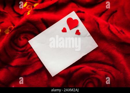 Carte blanche vierge avec petits coeurs rouges sur fond imprimé roses fleuries. Concept pour carte de mariage, fête de la Saint-Valentin, invitation, brochure, web resour Banque D'Images