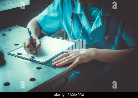 médecin mâle en uniforme bleu assis à une table et met un grand document podis Banque D'Images