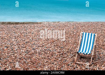 Une plage de galets déserte avec une chaise longue rayée vide au premier plan inférieur droit. Deux mouettes s'assoient sur un goyne en pierre en arrière-plan avec la mer Banque D'Images