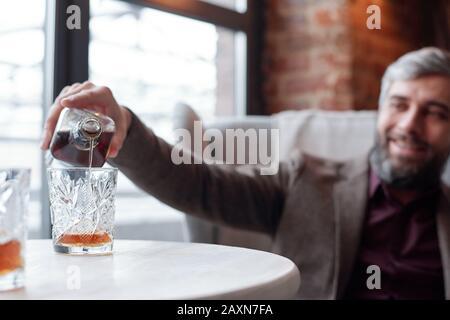 Gros plan de l'homme heureux qui verse du whisky dans le verre tout en se reposant dans le bar-salon Banque D'Images