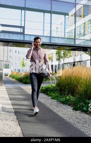 Un jeune homme devant un immeuble de bureaux moderne entend la musique