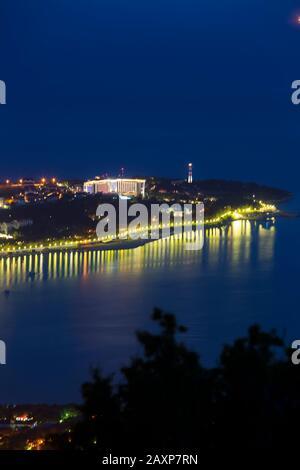 Baie de Gelendzhik, cap Épais et phare de Gelendzhik au crépuscule du soir depuis la vue des yeux des oiseaux. Les maisons sont visibles sur le Cap, et les lumières de Banque D'Images
