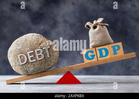 Ratio dette-PIB, une pierre importante avec DETTE de texte et cubes en bois avec lettres PIB et sac sur la mer Banque D'Images