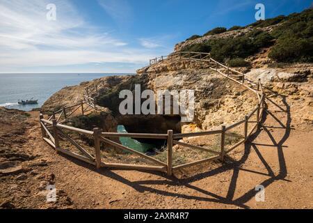 Trou de roche naturel sur le sentier de la falaise le long de la côte rocheuse de Praia da Marinha à Benagil, Algarve, district de Faro, Portugal Banque D'Images
