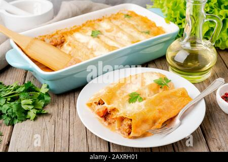 Cannelloni avec remplissage de bœuf haché, tomates, cuites avec sauce tomate bechamel, vue latérale, vieux fond en bois sombre Banque D'Images