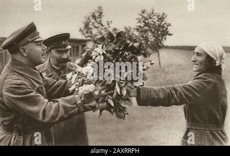 Armée rouge dans les années 1930. Du livre de propagande soviétique de 1937. Une femme soviétique ordinaire donne un bouquet de fleurs aux marshals Voroshilov et au maréchal Budyon Banque D'Images