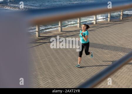Vue latérale à angle élevé d'une femme caucasienne d'âge moyen mûre qui travaille sur une promenade le jour ensoleillé, en course à pied Banque D'Images