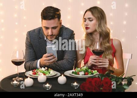 Femme Jalouse Randonnée Dans Le Smartphone De Boyfriend Pendant Le Dîner Au Restaurant Banque D'Images