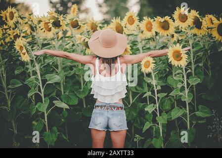 Vue arrière de la jeune femme à l'extérieur Sunflower Field Banque D'Images