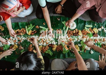 Top View portrait des gens asiatiques manger leur nourriture servie sur le dessus de la feuille de banane se poser sur le sol. Kembulan javanais tradition de manger