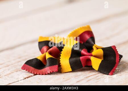 Des pâtes farfalles italiennes multicolores se rapproche sur une table rustique Banque D'Images
