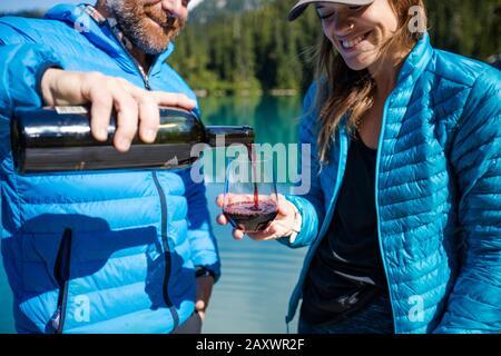 L'homme verse un verre de vin pour son partenaire au lac. Banque D'Images