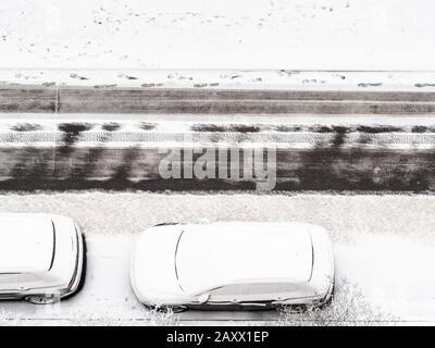 vue sur les voitures enneigées sur le bord de la route urbaine en hiver Banque D'Images