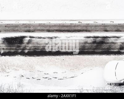 vue au-dessus des empreintes sur la route enneigée de la route urbaine défrichée en hiver Banque D'Images