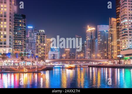 Nuit vue colorée sur la célèbre attraction touristique de la ville de Dubaï - Port maritime de Marina et gratte-ciel éclairés. Voyages et biens immobiliers en unité Banque D'Images